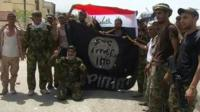 Iraqi soldiers and federal police hold the IS flag upside-down