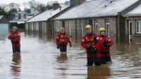 Rescue workers walking in flooded street