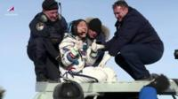 Christina Koch is lifted from the capsule