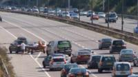 Boat being driven across three lanes of motorway traffic