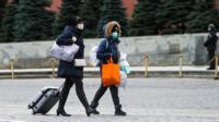 Люди в масках и с сумками на Красной площади.