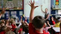 Anonymous pupils in class, hands raised
