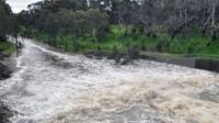 A torrent of water runs down a country road in Australia after the south of the country was hit by severe storms.