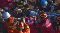 Survivor being stretchered from rubble
