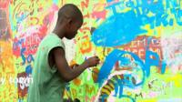 An artist boy painting in Ghana's capital, Accra
