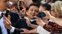 Zelensky takes a photo with a woman in the crowd