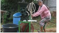 Guatemalan woman grinds corn using bicimaquina, or bicycle machine