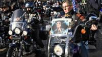 Hundreds of leather-clad bikers follow the French singer's coffin down the Champs-Elysees.
