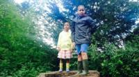 Jayden and Angel stood together on a tree stump