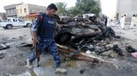 An Iraqi policeman walks past the site of a car bomb attack in Samawa