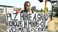 Jobless graduate Brian Radzuma holds a sign