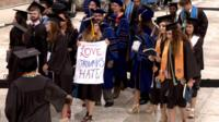 "Students, one holding a banner reading ""Love Trumps Hate"" leave as Mike Pence begins to speak at graduation ceremony (21 May)"