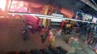 A CCTV grab shows fire pouring from part of the Kemerovo mall as visitors flee in panic