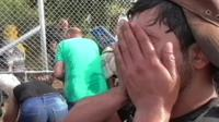 Man holding hands to his face after Hungarian police use tear gas to force back migrants on the Serbian-Hungarian border