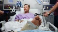 Neil Parker in a hospital bed surrounded by microphones