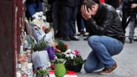 A man holds his head in his hands as he lays flowers