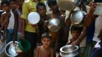 Indian villagers queue for food at the flood-hit Dagrua village