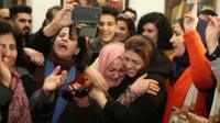 Afrah Shawqi al-Qaisi (2nd right) greeted by well-wishers following her release