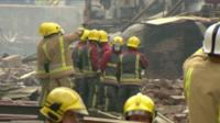 Firemen survey the wreckage of the flour mill