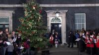 Theresa May turns on the Christmas lights in Downing Street with the help of three girls who won a competition to choose designs for the PM's Christmas card.