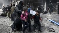 A Syrian woman and children run for cover amid the rubble of buildings following government bombing in the rebel-held town of Hamouria