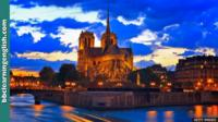An evening shot of Notre-Dame cathedral in Paris. It is illuminated by orange lighting.