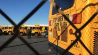 Los Angeles Unified School District buses stand idle in Gardena