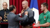 "French President Francois Hollande (L) awards U.S. Airman First Class Spencer Stone (C) with the Legion d""Honneur (the Legion of Honour) medal as U.S. National Guardsman Alek Skarlatos applauds"
