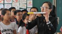 A woman holds up a large cigarette during an anti-smoking seminar in China