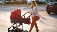 Woman crossing a road with a baby in the pram