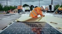 A person laying a solar PV (photovoltaic) panels on a road