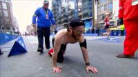 Marine Micah Herndon crawls on street during Boston Marathon