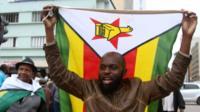 Protester holding Zimbabwe flag