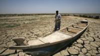 An Iraqi man walks past a canoe siting on dry, cracked earth in the Chibayish marshes near the southern Iraqi city of Nasiriyah