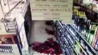 Broken bottles on floor of supermarket