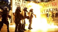 Riot police stand amongst flames from petrol bombs thrown by a small group of anti-establishment demonstrators in Athens
