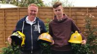 Andy and son John holding firefighter helmets