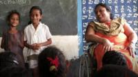 Sai Padma, right, sits in her wheelchair in a classroom full of children