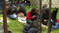 Migrants sitting on ground outside, behind fence