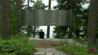A person sitting underneath the memorial to Breivik's victims
