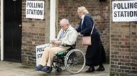 Polling station with a wheelchair user leaving the building, being pushed