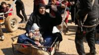 Woman and child being pushed on cart