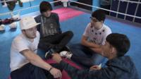 The School Reporters sit in the ring with Carl Jones, who gives them some advice