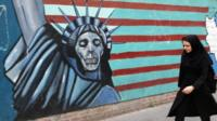 An Iranian woman walks past a mural on the wall of the former US embassy in the Iranian capital