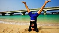 An 84-year-old man doing yoga on a beach in Japan