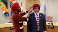 Gurdeep Pandher fits Mayor Dan Curtis with a turban