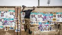 Man climbs up wall with election posters