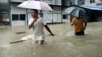 People wade through a flooded street at a town hit by Typhoon Soudelor in Ningde, Fujian province, China