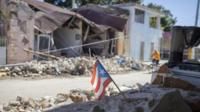 A Puerto Rican flag stands amoungst earthquake debris