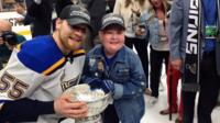 Superfan with Blues player on ice
